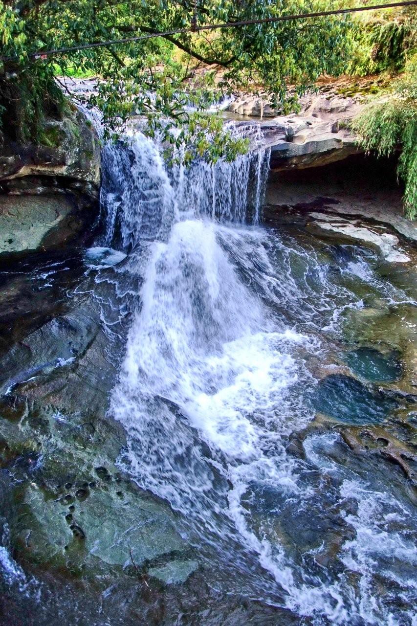 ▲瀑水潺潺的眼鏡洞瀑布,因2個河蝕大窟窿而得名。